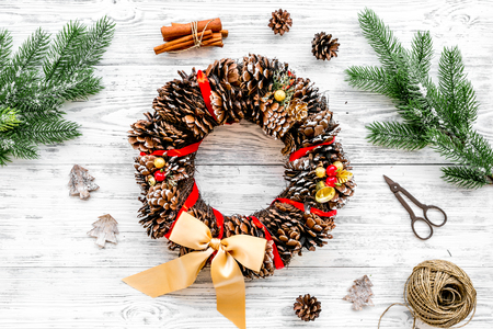 Festive christmas wreath made of pine cones near spruce branch for decorate home on white wooden background top view.
