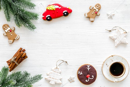 Festive New Year candies. Traditional gingerbread cookies in different shape for decoration new year tree near coffee on white background top view.