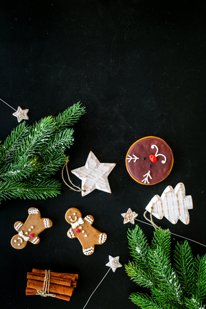 Festive New Year candies. Traditional gingerbread cookies in different shape for decoration new year tree on black background top view.