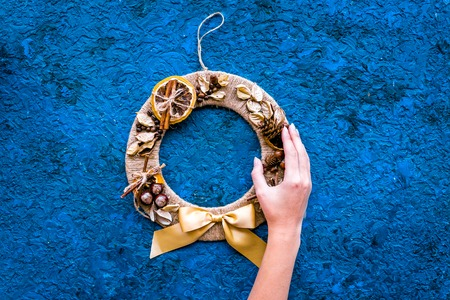 Hand hang a creative christmas wreath made of thread, dry fruits and nuts on blue background top view.