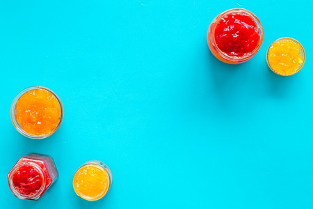 Set of sweet jams in glass jars on blue background top view copy space Stock Photo