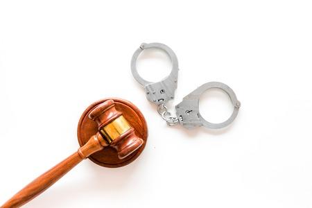 Arrest concept. Metal handcuffs near judge gavel on white background top view.