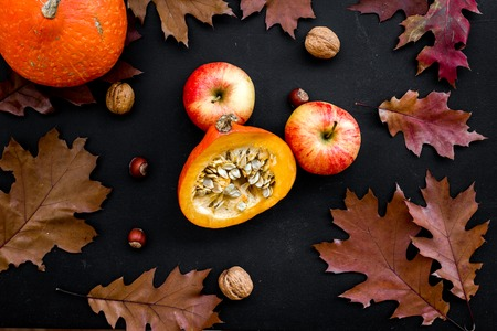 Autumn background. Dried leaves, pumpkin, apple and nuts on black background top view.