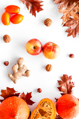 Autumn garden harvest. Dried leaves, pumpkin, apple, tomatoes, ginger and nuts on white background top view.