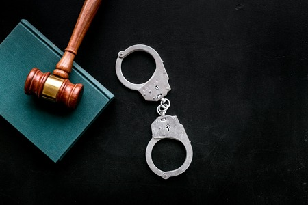 Arrest concept. Metal handcuffs near judge gavel and law book on black background top view.