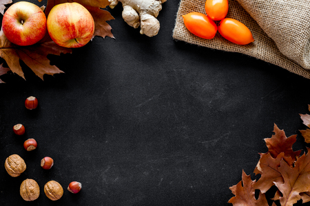 Autumn nature concept. Background with autumn symbols. Brown leaves, nuts and apple on black background top view. Stock Photo