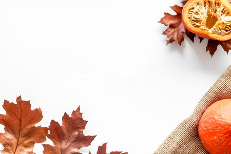 Autumn nature concept. Background with autumn symbols. Brown leaves, pumpkin, nuts on white background top view.
