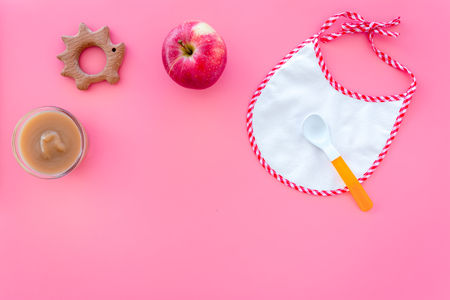 Baby food concept. Apple puree in bowl near bib, apple, spoon on pink background top view space for text