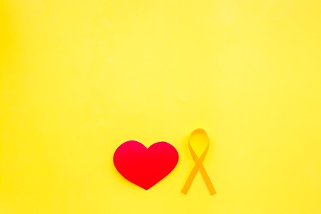 Endometriosis. Gynecological diseases concept. Symbolic yellow ribbon near heart sign on yellow background top view copy space