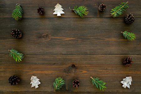 New Year frame made of pine sprigs, cones, spruce figure, fir oil on dark wooden background top view copy space