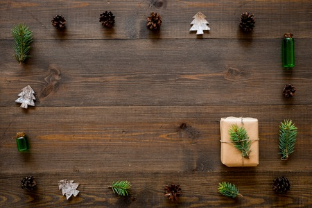 New Year gift decorated with craft paper and pine sprout in frame of spruce branch, pine cones, spruce cutout on dark wooden background top view copy space