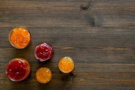 Set of sweet jams in glass jars on dark wooden background top view copy space