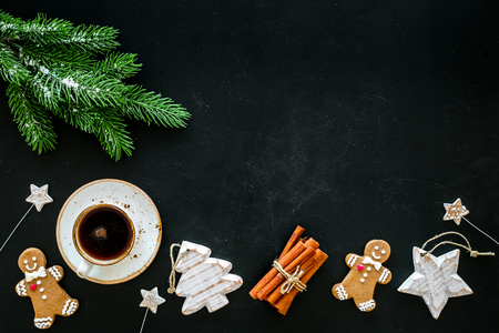 New Year composition with sweets. Gingerbread cookies in shape of man, spruce, star near coffee, spruce branch, festive decoration on black background top view space for text