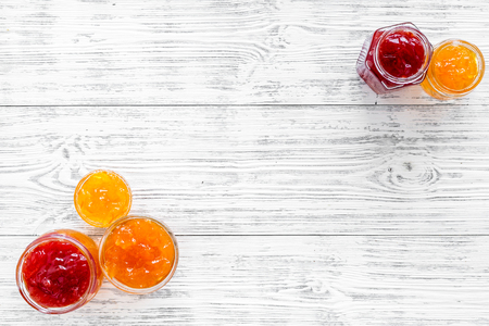 Set of sweet jams in glass jars on white wooden background top view space for text
