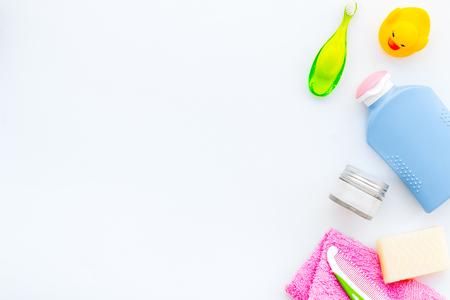 Kit de cuidado personal para niños. Accesorios de baño con cepillo de dientes y patito de goma amarillo sobre fondo blanco, espacio de vista superior para texto
