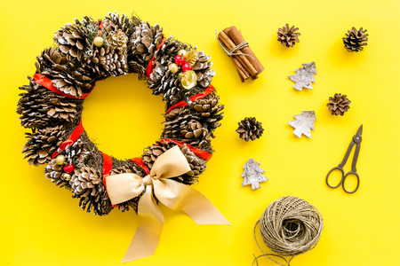 Christmas decoration concept. Christmas wreath made of pine cones near matherials and instruments, sciccors on yellow background top view
