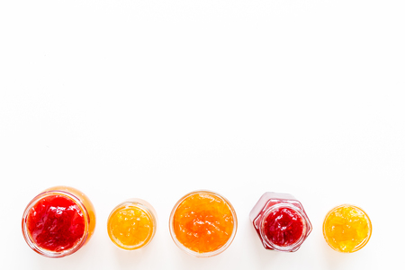 Set of sweet jams in glass jars on white background top view copy space