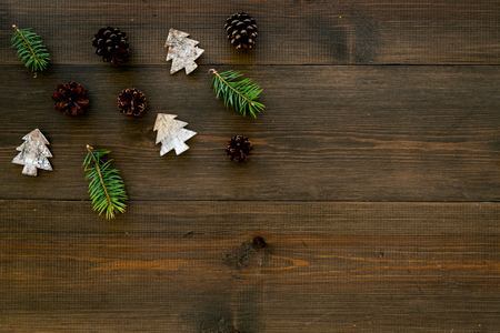 Winter ornament, New Year pattern. Pine sprigs, cones, spruce figure, fir oil on dark wooden background top view space for text