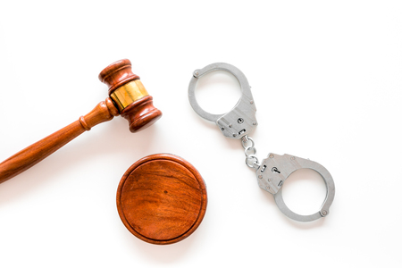Arrest concept. Metal handcuffs near judge gavel on white background top view copy space