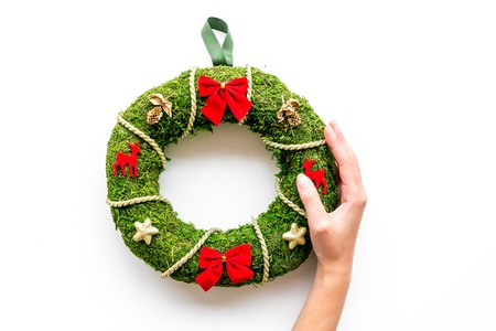 Hand hang a classic christmas wreath on white background top view.