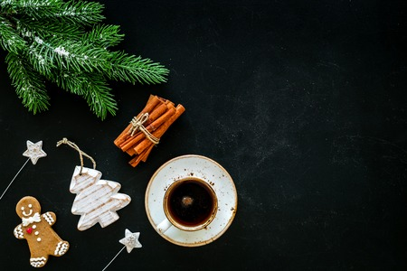 New Year composition with sweets. Gingerbread cookies in shape of man, spruce near coffee, spruce branch, festive decoration on black background top view.