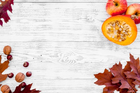 Composition with autumn vegetables and leaves in red and orange colors. Brown dried leaves, pumpkin, apple on white wooden background top view copy space