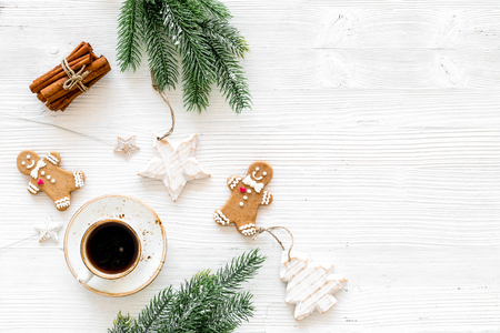 New Year composition with sweets. Gingerbread cookies in shape of man, spruce, star near coffee, spruce branch, festive decoration on white background top view copy space