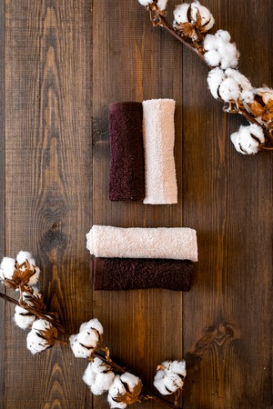 Cotton towels high quality. Set of towels twisted coil near dry cotton flowers on dark wooden background top view Imagens