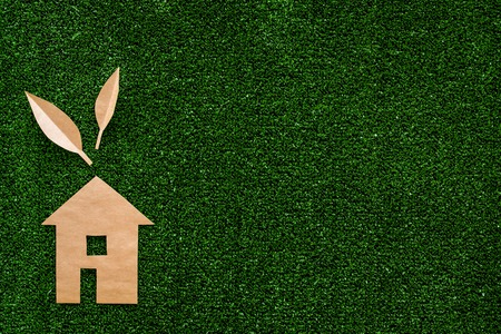 Green energy for home concept. Care for environment. House cutout made of craft paper on green grass background top view.