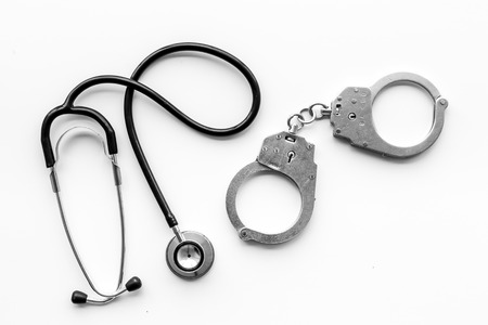 Medical lawsuit. Arrest for medical crime concept. Handcuff near stethoscope on white background top view.