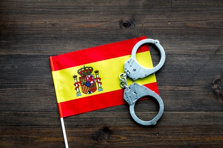 Violation of law, law-breaking concept. Metal handcuffs on Spanish flag top view.