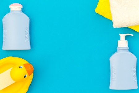 Hygiene items for the child. Bath accessories with yellow rubber duck on blue background top view. Stock Photo