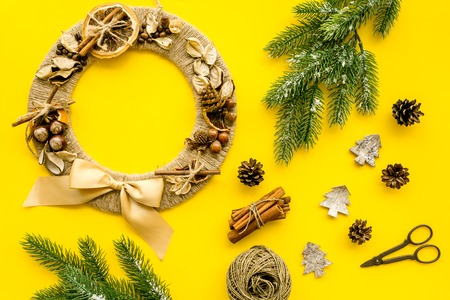 Process of making christmas wreath concept. Creative christmas wreath made of thread near matherials and instruments, sciccors on yellow background top view.