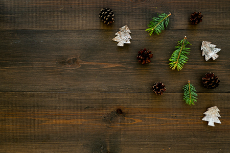 Winter ornament, New Year pattern. Pine sprigs, cones, spruce figure, fir oil on dark wooden background top view. Stock fotó