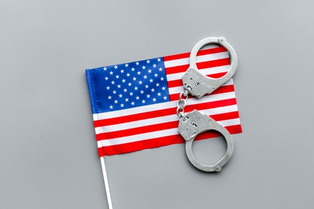 Violation of law, law-breaking concept. Metal handcuffs on American, USA flag top view.