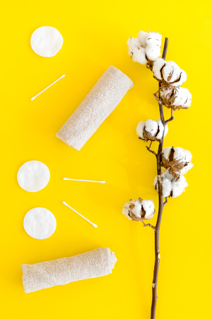 Cotton hygiene products. Cotton pads and swabs, towels twisted coil near dry cotton flowers on yellow background top view.