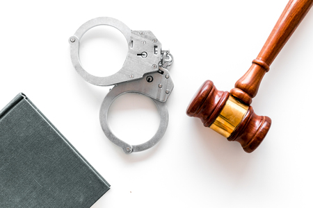 Crime concept. Metal handcuffs near judge gavel and law book on white background top view.