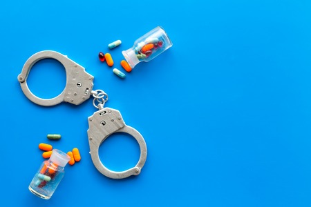 Arrest for illegal purchase, possession and sale drugs concept. Drugs as pills near handcuff on blue background top view.