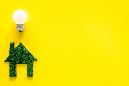 Enegry saving technology concept. House cutout made of green grass near light bulb on yellow background top view. Imagens