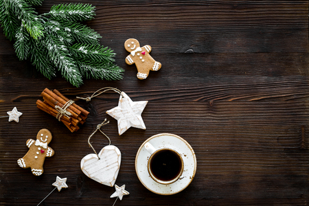New Year gingerbread cookies. Gingerbread man near coffee, spruce branch, festive decoration on dark wooden background top view copy space