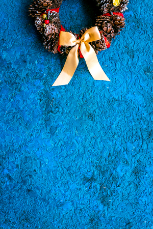 Christmas wreath made of pine cones on blue background top view copy space Stock Photo