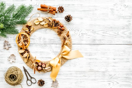 Preparing to Christmas. Creative Christmas wreath made of thread near decorative elements on white wooden background top view copy space