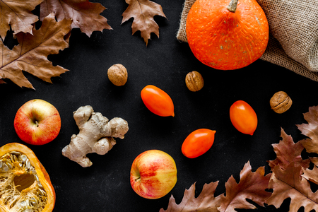 Autumn garden harvest. Dried leaves, pumpkin, apple, tomatoes, ginger and nuts on black background top view Stock Photo