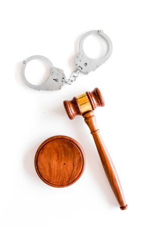 Arrest concept. Metal handcuffs near judge gavel on white background top view