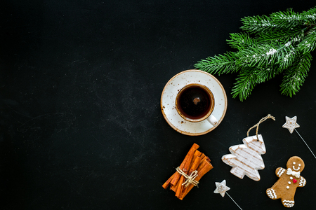 New Year composition with sweets. Gingerbread cookies in shape of man, spruce near coffee, spruce branch, festive decoration on black background top view space for text