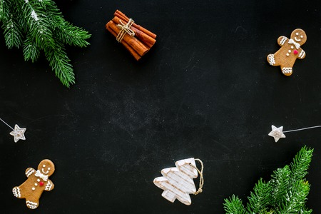 New Year gingerbread cookies. Gingerbread man near coffee, spruce branch, festive decoration on black background top view copy space frame Foto de archivo