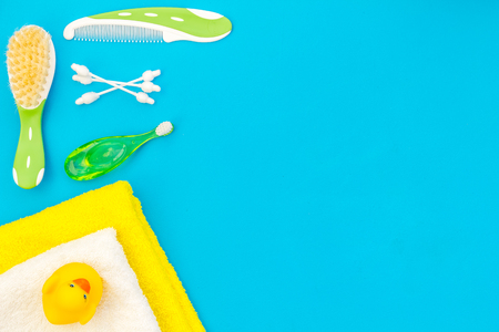 Childrens personal care kit. Bath accessories with teeth brush and yellow rubber duck on blue background top view space for text
