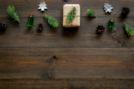 New Year pattern with pine sprigs, cones, spruce figure, fir oil and new year gift decorated with craft paper and pine sprout on dark wooden background top view copy space Stock Photo