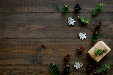 Background with New Year gift. Box wrapped in craft paper, decorated with pine sprig and cones on dark wooden background top view space for text