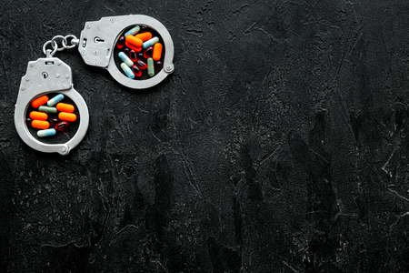 Arrest for illegal purchase, possession and sale drugs concept. Drugs as pills near handcuff on black background top view space for text Stock fotó - 111574808